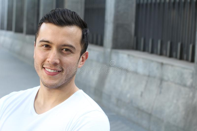 Zamyka w górę portreta młody latynoski nastolatka mężczyzna patrzeje kamerę z radosnym uśmiechniętym wyrażeniem, przeciw miastowe obrazy royalty free