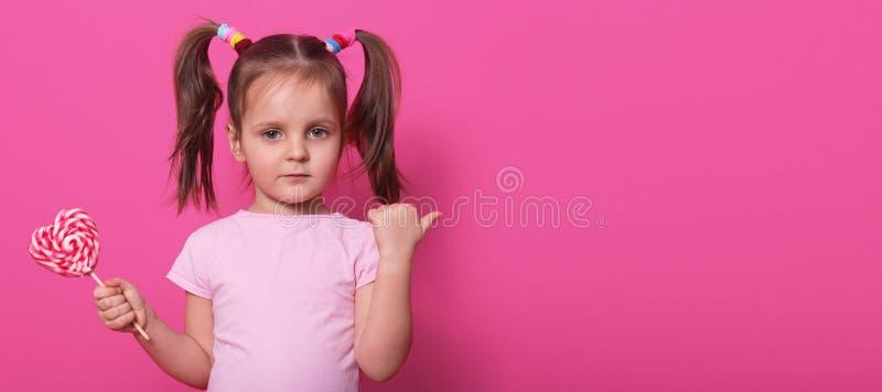 Zamyka w górę portreta mały śliczny dziecko, patrzejący bezpośrednio przy kamerą, trzymający kierowego jaskrawego lizaka, wskazuj obrazy stock
