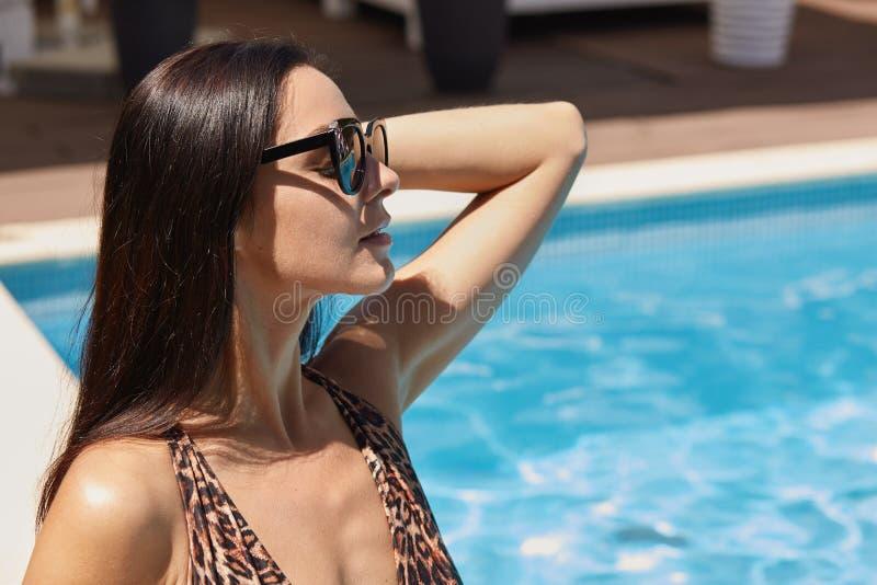 Zamyka w górę portreta marzycielska romantyczna kobieta pozuje nad czystej wody tłem, chłodzący blisko basenu, dotyka jej włosy obraz royalty free