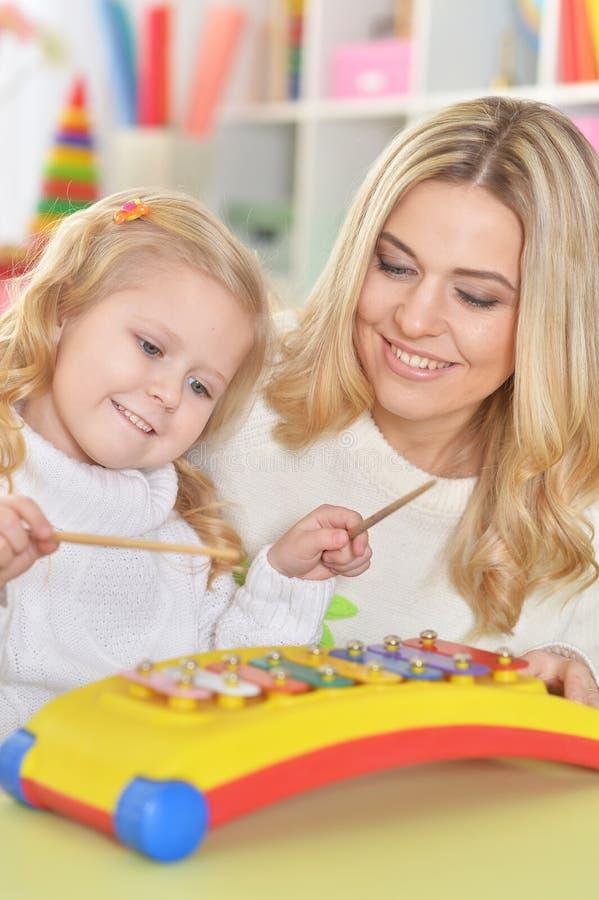 Zamyka w górę portreta matka z małą córką bawić się na instrumencie muzycznym obraz royalty free