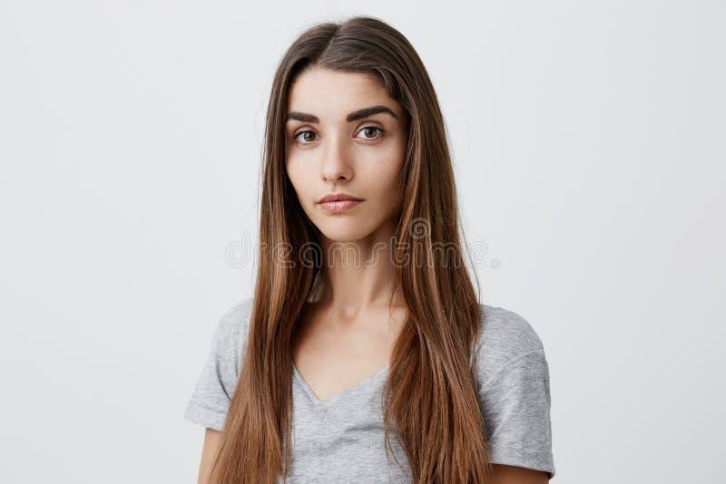 Zamyka w górę portreta piękna poważna ciemnowłosa caucasian kobieta z długą fryzurą w przypadkowy szary koszulowy patrzeć wewnątr obrazy royalty free