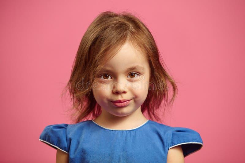 Zamyka w górę portreta powabna mała dziewczynka z poważnym spojrzeniem na menchiach odizolowywać obrazy royalty free