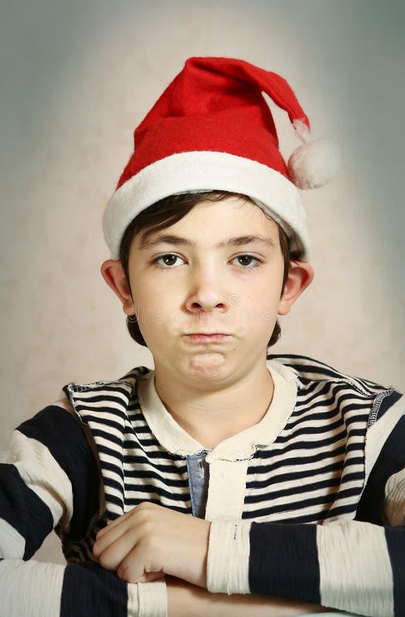 Zamyka w górę portreta preteen chłopiec w Santa kapeluszu zdjęcia stock