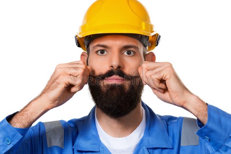 Zamyka w górę portreta przystojny brodaty budowniczy w ciężkim kapeluszu, brygadierze lub repairman w hełmie bawić się z jego wąs obrazy stock