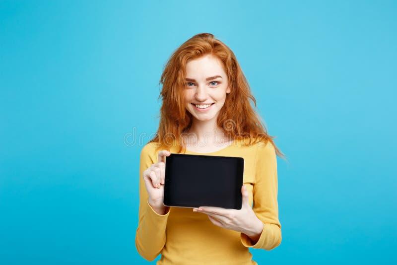 Zamyka w górę portreta redhair młodej pięknej atrakcyjnej dziewczyny ono uśmiecha się pokazywać cyfrowego pastylka ekran na czern obraz stock