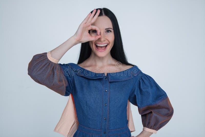 Zamyka w górę portreta uśmiechnięta brunetki kobieta z białymi zębami, patrzeje kamerę przez palców w ok gescie być ubranym modę zdjęcia stock