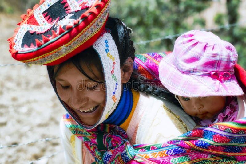 Zamyka w górę portreta uśmiechnięta Quechua kobieta ubierająca w kolorowym tradycyjnym handmade stroju i nieść jej dziecka w temb obraz stock