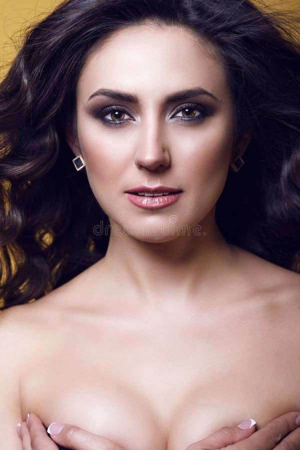 Zamyka w górę portreta w średnim wieku piękna brunetka z perfect makijażem i nagimi ramionami zakrywa jej pierś z ona ręki obraz royalty free