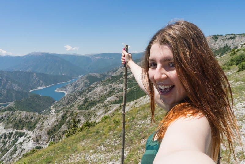 Zamyka w górę portreta wycieczkowicza dziewczyny uśmiechniętego i roześmianego mienia drewniany kij Excursionist czerwieni głowy  zdjęcia stock