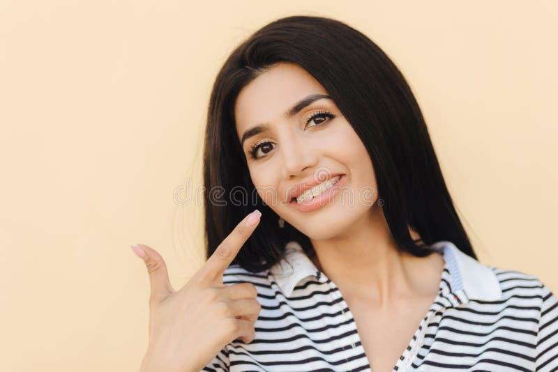 Zamyka w górę portreta zadowolona brunetki kobieta z ciemnymi oczami, ładnego uzupełniał, wskazuje przy usta, szerokiego uśmiech, zdjęcie stock