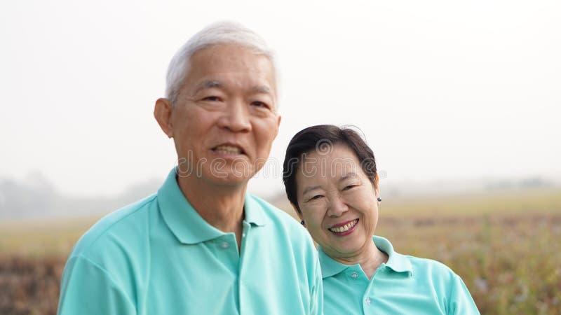 Zamyka w górę potrait uśmiechnięta Azjatycka starsza para na jaskrawym - zieleń obraz royalty free