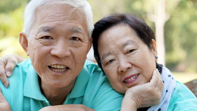 Zamyka w górę potrait uśmiechnięta Azjatycka starsza para na jaskrawym - zieleń fotografia stock