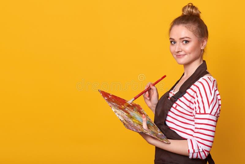 Zamyka w górę profilowego portreta szczęśliwy żeński artysta, trzymający paletę i paintbrush w rękach, stoi przeciw żółtemu studi obrazy stock