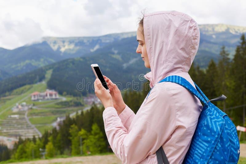 Zamyka w górę profilowego portreta wycieczkowicz młoda kobieta z błękitnym plecakiem bierze fotografie piękny krajobraz góra w wi zdjęcia royalty free