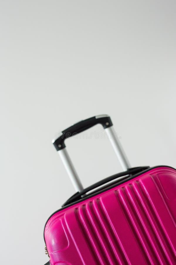 zamyka w górę różowej plastikowej walizki nad białym tłem z kopii przestrzenią obraz stock