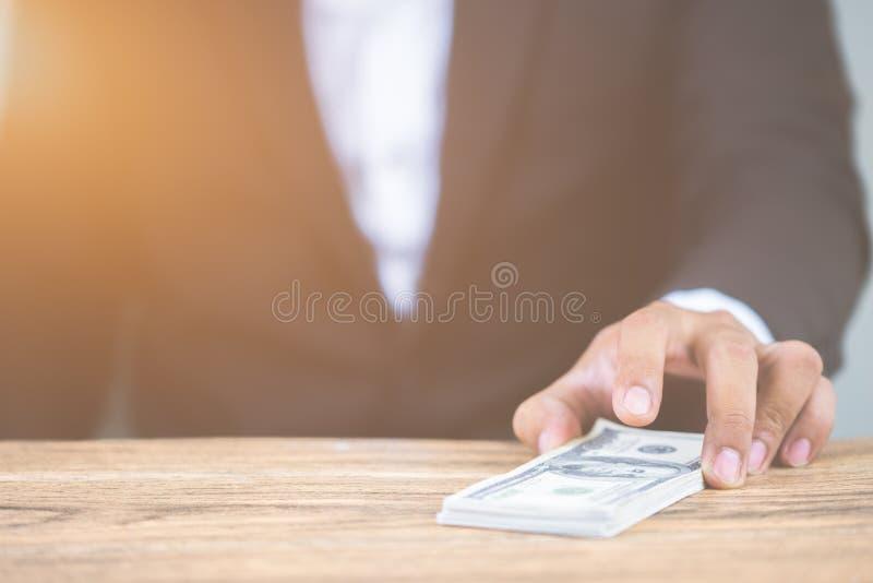 Zamyka w górę ręki biznesmena mienia pieniądze dolarowi rachunki na drewnianym stole Używać jako pojęcie korupcja obraz royalty free
