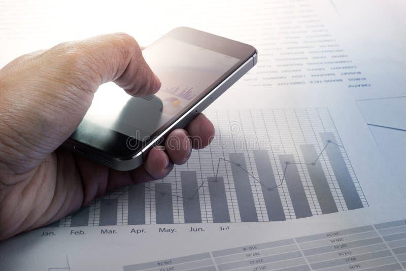 Zamyka w górę ręki biznesmena wzruszający smartphone wykres i fotografia stock