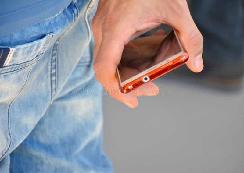 zamyka w górę ręki mężczyzna trzyma jego telefon między jego palcem Mężczyzna ręka jest przy jego z powrotem Jest żadny używać je fotografia stock