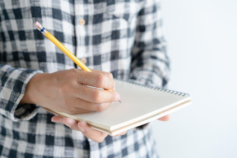 zamyka w górę ręki pisze papierowym notatniku na Na młodej kobiety lewej ręki mienia notatniku i prawa ręka pisze dzienniczku obraz royalty free