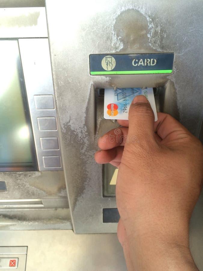 Zamyka w górę ręki trzyma mistrzowską kartę lub karta banka ATM maszyna obrazy royalty free
