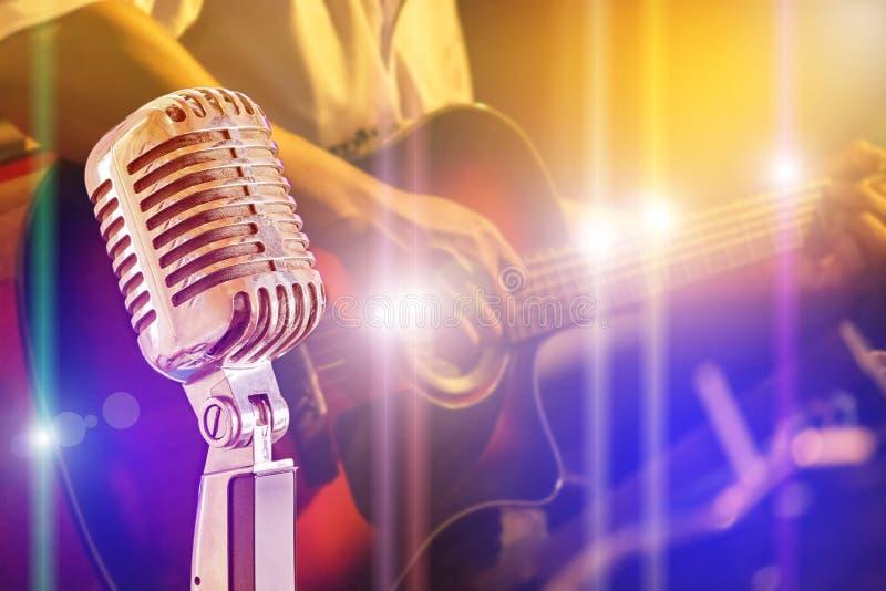 Zamyka w górę retro mikrofonu z muzykiem bawić się gitarę akustyczną na zespole zdjęcia stock