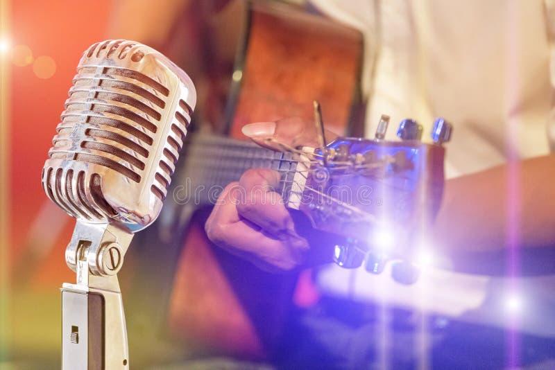 Zamyka w górę retro mikrofonu z muzykiem bawić się gitarę akustyczną na zespole zdjęcie stock