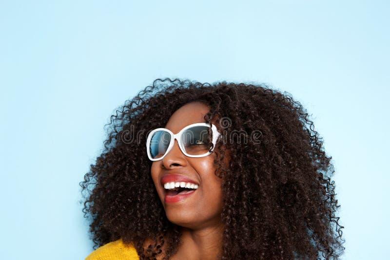 Zamyka w górę rozochoconej młodej afrykańskiej kobiety patrzeje oddalony i śmia się na błękitnym tle w okularach przeciwsłoneczny zdjęcia stock
