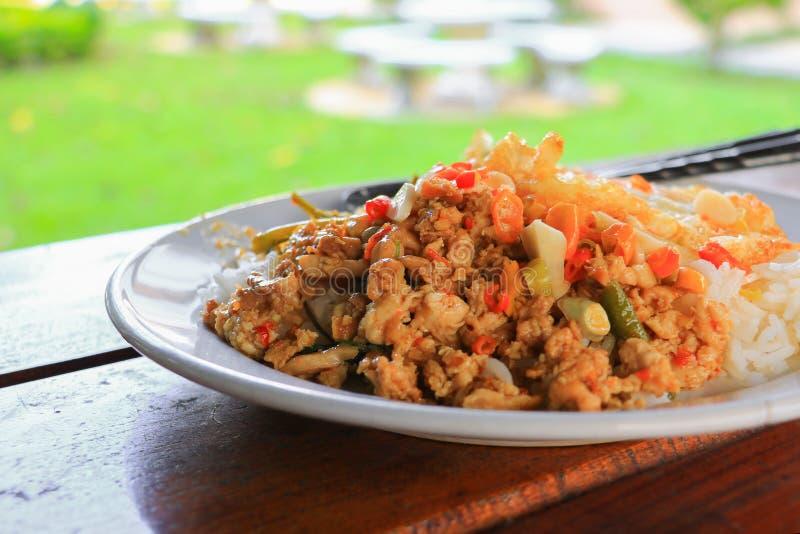 Zamyka w górę ryż nakrywających z kurczaka basilu Thailand korzennym jedzeniem Na drewnianym biurku obraz royalty free