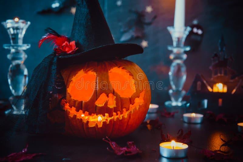 Zamyka w górę rzeźbiącej bani w czarownica kapeluszu i tapetuje sylwetki nietoperze, płonące świeczki, kasztel, duchy na czerń ka obraz royalty free