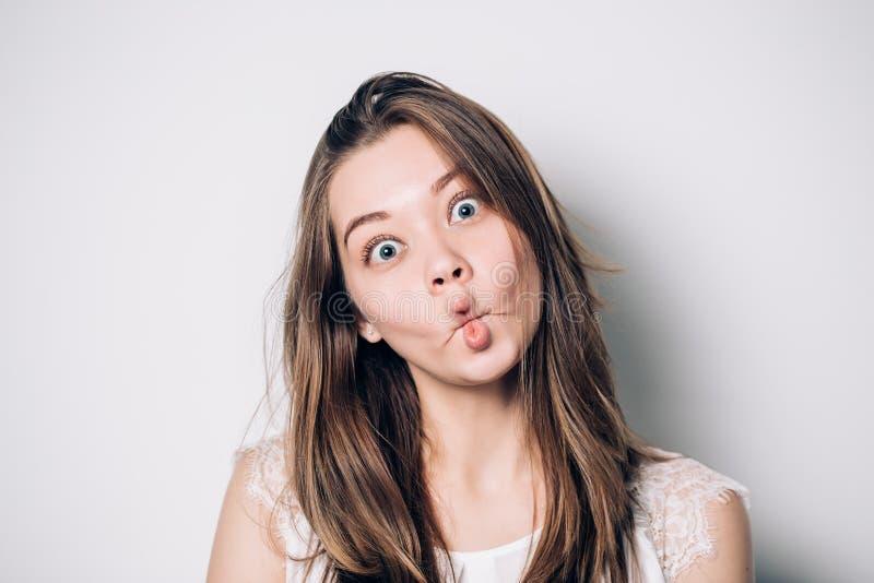 Zamyka w górę salowego portreta chłodno ładna młoda brunetki dziewczyna kobieta błaź się wokoło, robić szalonemu śmiesznemu gryma fotografia stock