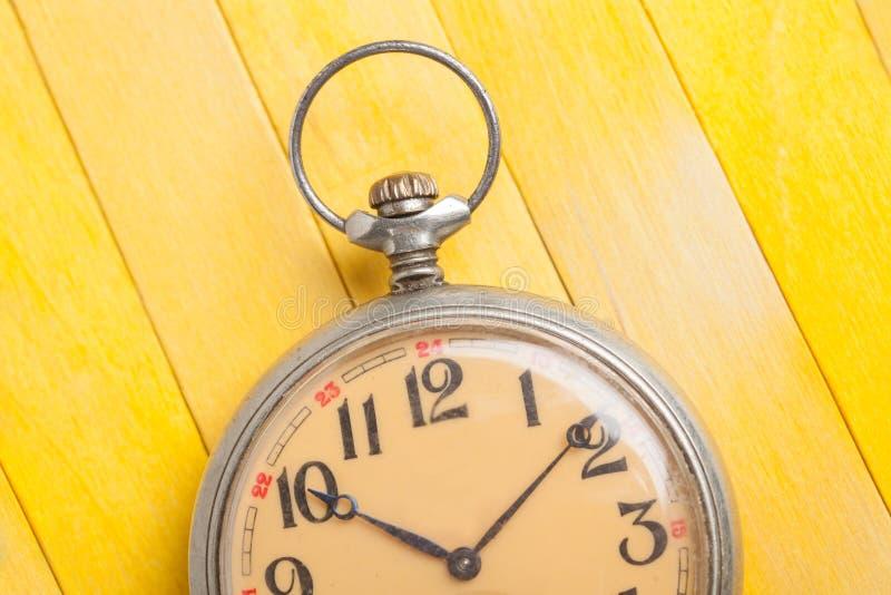 Zamyka w górę starego stylu kieszeniowego zegarka na żółtym drewnianym backround obrazy stock