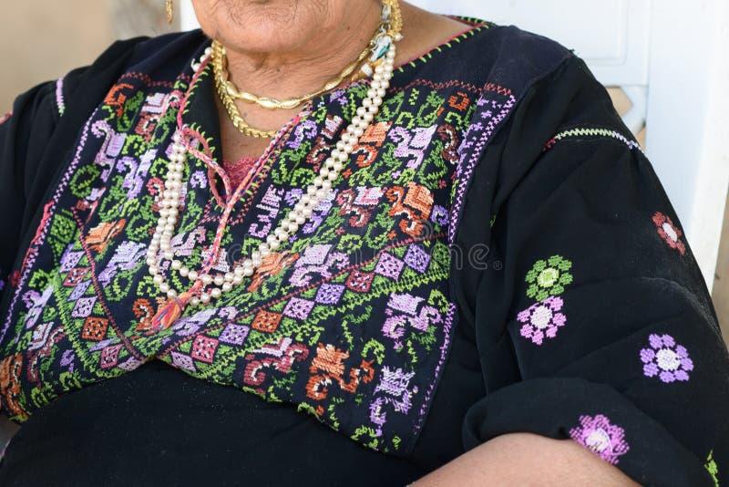 Zamyka w górę starej Arabskiej kobiety z tradycyjnym arabskim smokingowym obsiadaniem na krześle fotografia stock