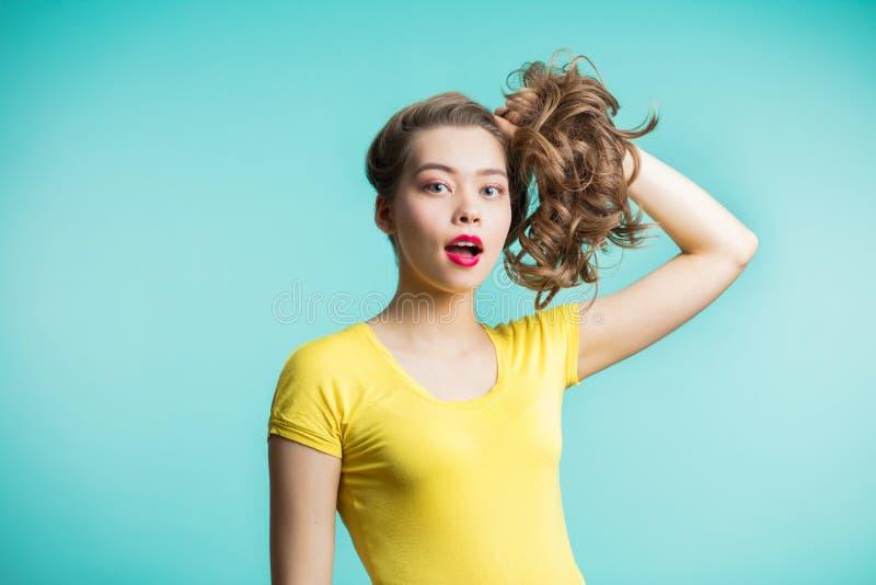 Zamyka w górę strzału ono uśmiecha się przeciw błękitnemu tłu elegancka młoda kobieta Piękny model zbierający kobieta włosy spojr obraz stock