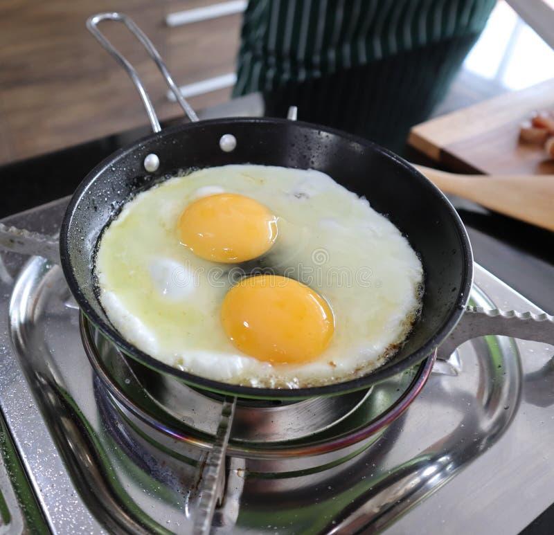 Zamyka w górę strzału smażący niecek jajka na storve w kuchni fotografia royalty free