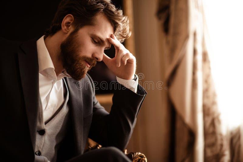 Zamyka w górę strzału zadumany brodaty mężczyzna w eleganckim formalnym kostiumu, rozpamiętywa o coś, niektóre problemy z finansa obrazy stock