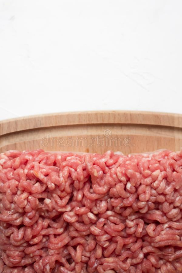 zamyka w górę Surowego Minced mięsa na tnącej desce i kuchennego ręcznika na białym stole zdjęcie royalty free