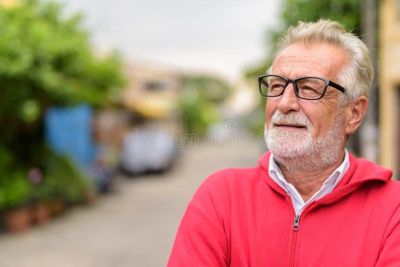 Zamyka w górę szczęśliwego przystojnego starszego brodatego mężczyzny ono uśmiecha się podczas gdy cienki zdjęcia royalty free