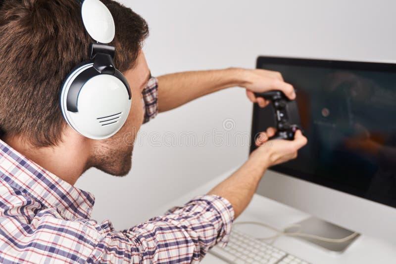 Zamyka w górę szczegółu młody brodaty męski gamer bawić się gry na osobistym komputerze z kontrolerem w hełmofonach, opowiada obrazy royalty free
