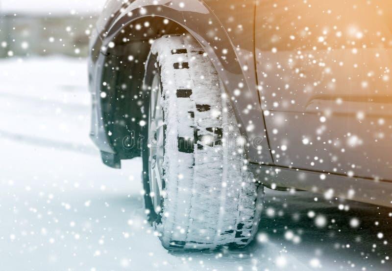 Zamyka w górę szczegółu samochodowego koła z nowym czarnym gumowej opony ochraniaczem na zimy śnieg zakrywającej drodze Transport obrazy stock