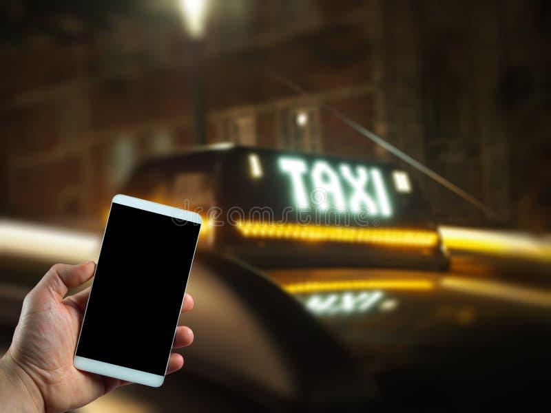 Zamyka w górę telefonu komórkowego na ręki i taxi samochodu tle obrazy stock