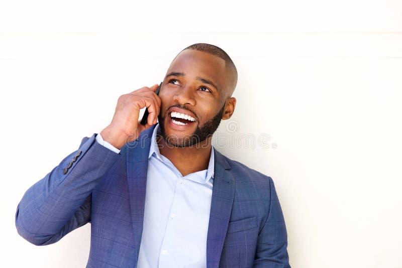 Zamyka w górę uśmiechniętego afrykańskiego biznesmena opowiada na telefonie komórkowym fotografia royalty free