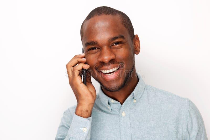 Zamyka w górę uśmiechniętego młodego murzyna opowiada z telefonem komórkowym przeciw odosobnionemu białemu tłu obrazy stock