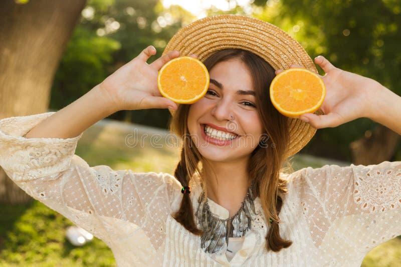 Zamyka w górę uśmiechniętej młodej dziewczyny w lato kapeluszowym wydaje czasie przy parkiem, pokazywać pokrojonego orang obrazy stock