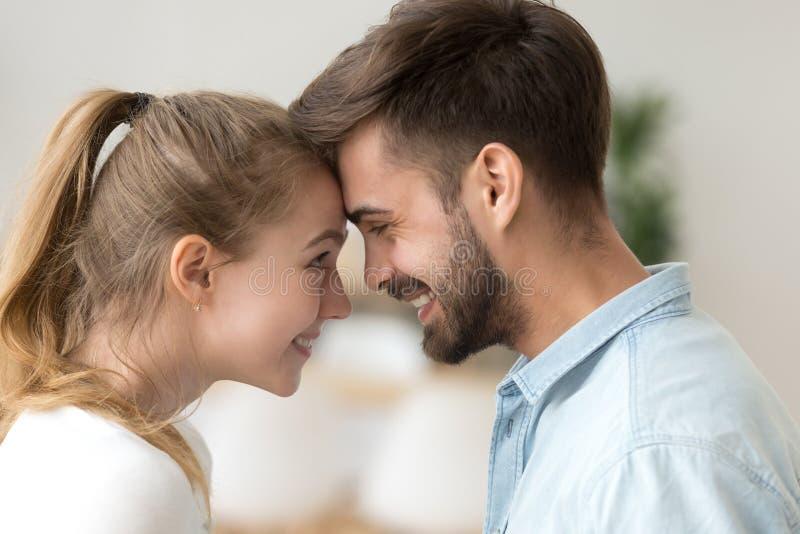 Zamyka w górę uśmiechniętej pary w miłości wzruszającym czole, cieszy się czułego moment zdjęcie royalty free