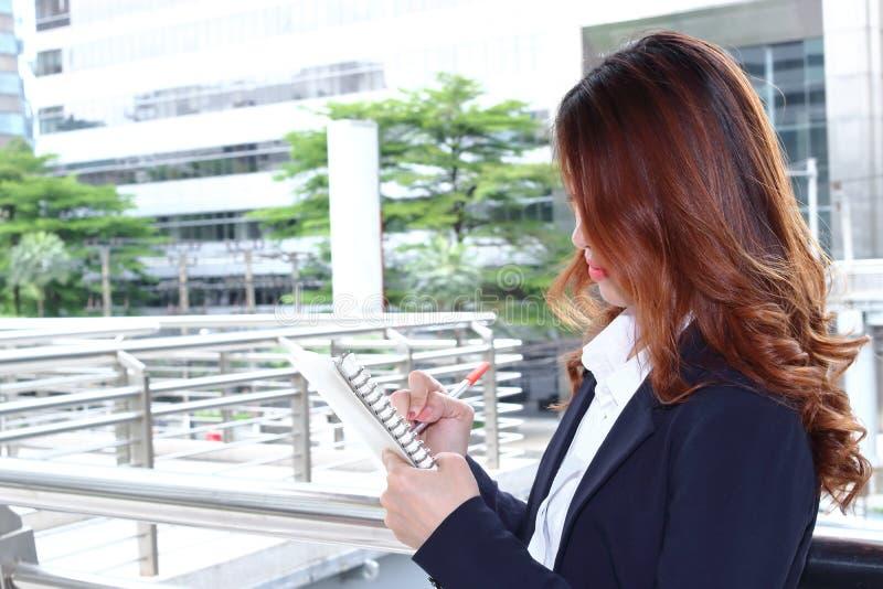 Zamyka w górę ufnego Azjatyckiego sekretarki kobiety writing na notatniku o pracie przy placem budowy fotografia royalty free