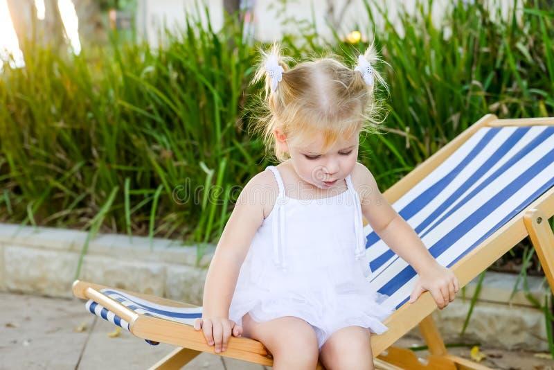 Zamyka w górę Uroczej blondy dziewczynki w dziecka obsiadaniu i relaksować na sukni lub berbecia sunbed lub deckchair w miasto pa zdjęcie stock