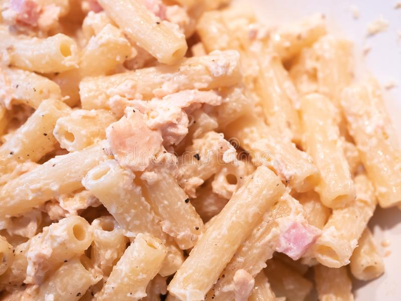 Zamyka w górę Włoskiego makaronu z łososiem, pomidor, czerwona cebula, olej, pieprzowa śmietanka obraz royalty free