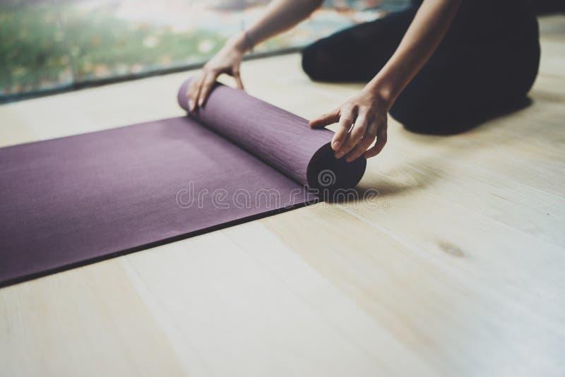 Zamyka w górę widok żeńskie ręki Wspaniałej młodej kobiety ćwiczy joga salowy Piękne dziewczyny narządzania maty dla praktyki zdjęcie royalty free