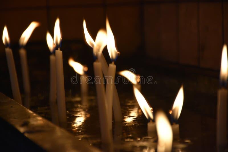 Zamyka w górę widoku świeczki pali jaskrawy w zmroku zdjęcie stock