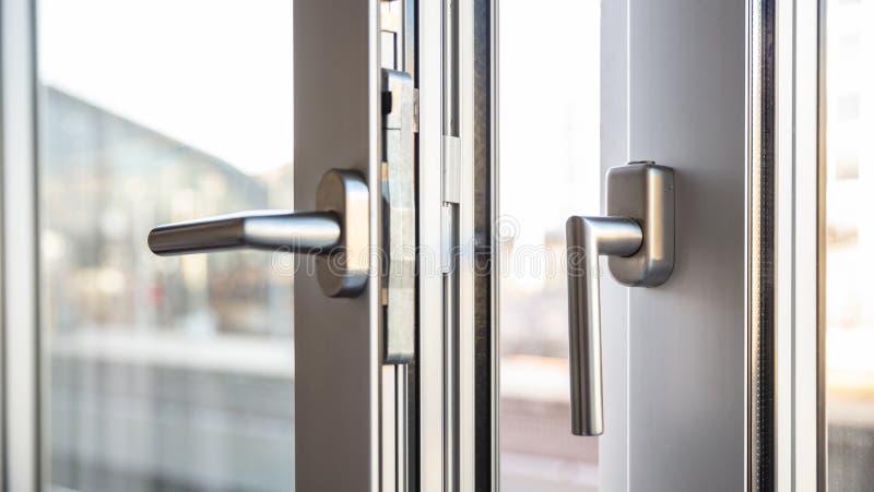 Zamyka w górę widoku aluminiowe drzwiowe nadokienne rękojeści, przeciw rozmytemu fotografia stock